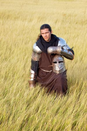 Medieval knight in the field with a helmet photo
