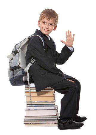 ni�os saliendo de la escuela: Colegial sentado en libros aislados en un fondo blanco  Foto de archivo