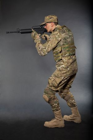 Soldier with rifle on a black background Stock Photo - 7742523