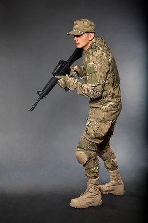 Soldier with rifle on a black background Stock Photo - 7742524