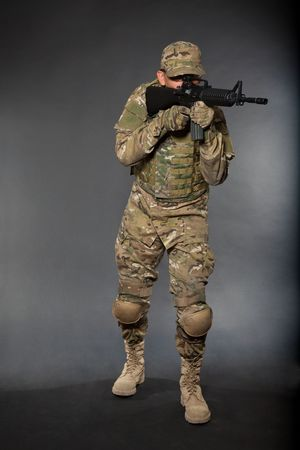 Soldier with rifle on a black background Stock Photo - 7742519