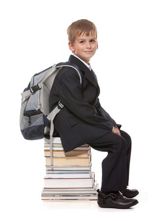 Schoolboy sitting on books isolated on a white background Stock Photo - 7853229