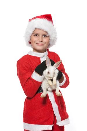 Boy holding a christmas rabbit isolated on white background photo
