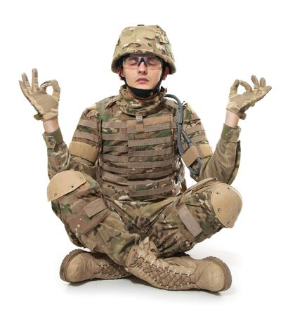 Modern soldier meditating. Isolated on a white background photo