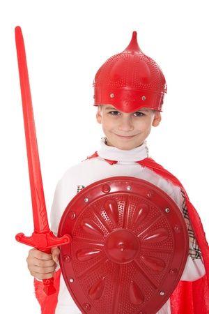 small sword: Young Boy Dressed Like a knight holding a sword and shield isolated on white