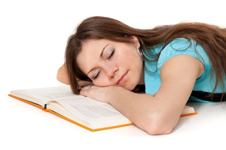 Beautiful student is sleeping on the book isolated on white photo