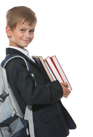 elementary age boy: Boy holding books isolated on a white background Stock Photo