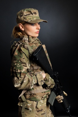 sniper: Beautiful army girl with rifle isolated on black