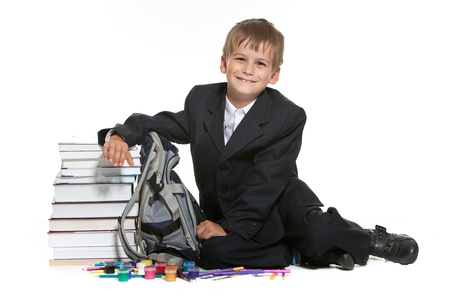 Boy, pencils, paints and books isolated on a white background photo