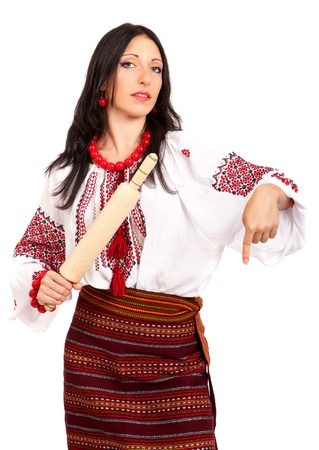Angry housewife with rolling pin. Woman wears Ukrainian national dress isolated on white background photo