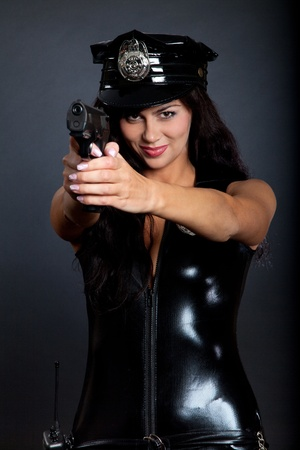 Beautiful sexy police girl with handgun and handcuffs, isolated on black background