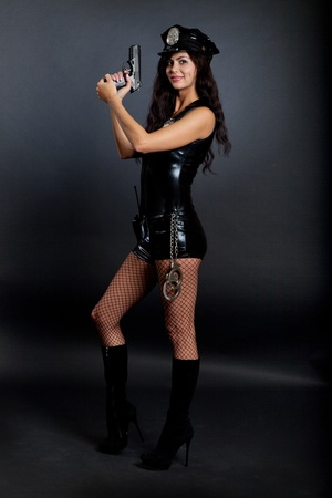 Beautiful sexy police girl with handgun and handcuffs, isolated on black background Stock Photo - 10655211
