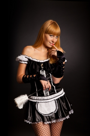 Beautiful caucasian woman dressed in a French Maid costume isolated on a black background photo