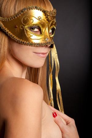 carnaval masker: Foto van een jonge vrouw, gekleed masker geïsoleerd op een zwarte achtergrond