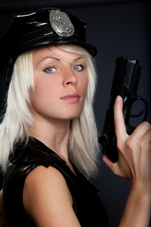 Beautiful sexy police girl with handgun and handcuffs, isolated on black background  photo