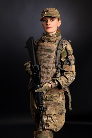 protective suit: Beautiful army girl with rifle isolated on black