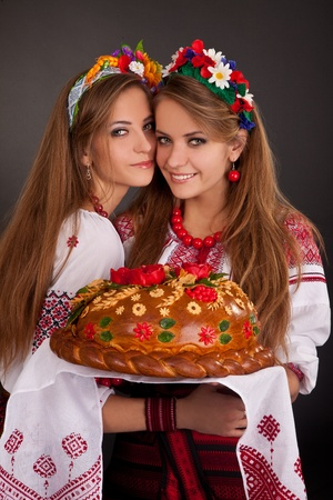 national cultures: Young women in ukrainian clothes, with garland and round loaf