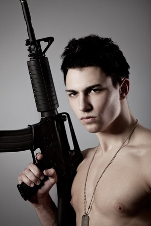 Handsome bare-chested soldier is holding a rifle on black background Stock Photo - 12015283