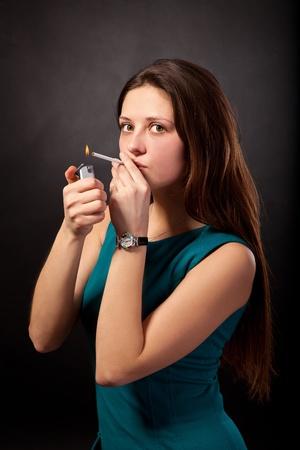 encendedores: Joven y bella mujer est� fumando cigarrillos sobre fondo negro