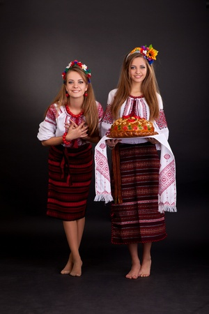 Young women in ukrainian clothes, with garland and round loaf Stock Photo - 12386748
