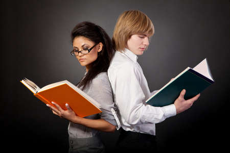 Two students are reading books on a black background photo