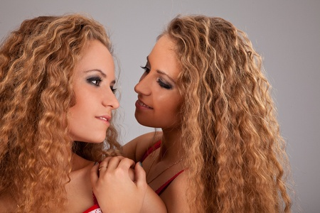 Sttudio shot portrait on isolated background of two sisters twin women friends photo