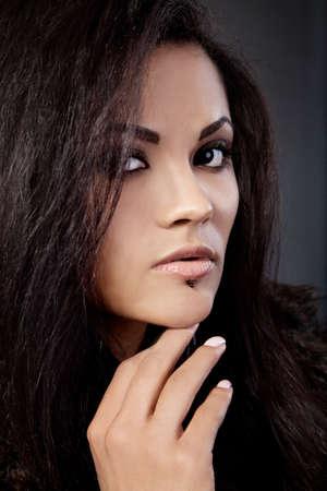 mulato: Retrato de mujer atractiva raza mixta con la mano en la barbilla sobre un fondo negro Foto de archivo