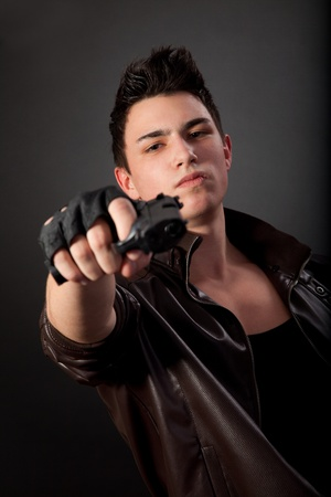 gunman: Aiming. Serious man with a gun on a black background Stock Photo
