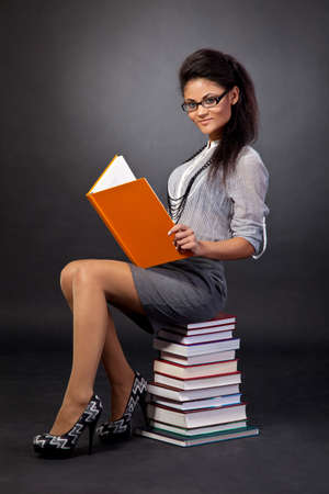 Cute mixed race student girl reading while sitting on heap of books on a black background photo