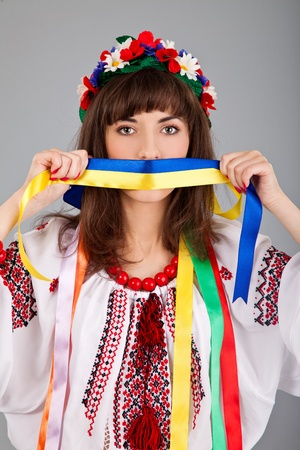 Cute Ukrainian  woman with blue yellow band on the mouth isolated on a gray background photo
