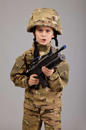 Young boy dressed like a soldier with rifle isolated on gray background photo