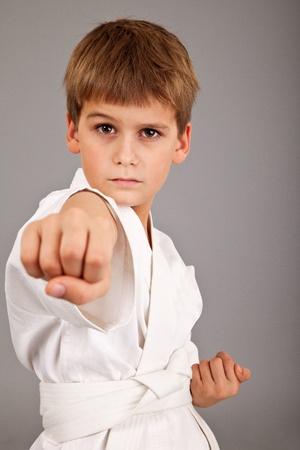 Karate boy in white kimono fighting isolated on gray background photo