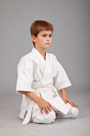Karate boy in white kimono is sitting isolated on gray background photo