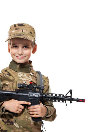 Young boy dressed like a soldier with rifle isolated on white  photo