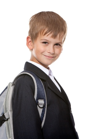 Schoolboy sitting on books isolated on a white background photo