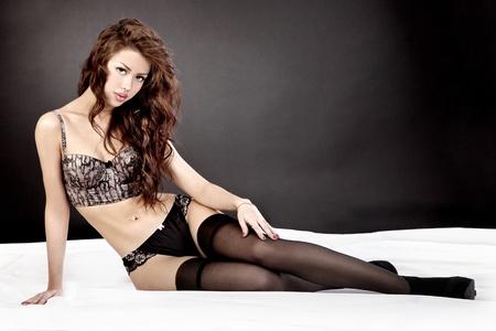 mujeres eroticas: Retrato de la hermosa mujer sonriente joven tumbado en la cama en ropa interior.
