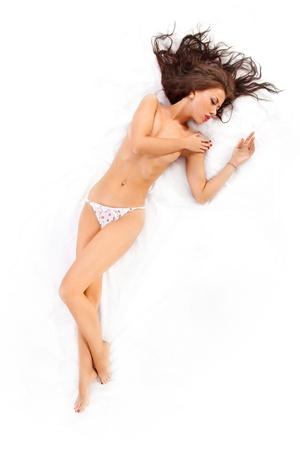 sexy girl nue: Portrait en pied d'une femme nue flirt allong� sur le lit. Tourn� dans un studio