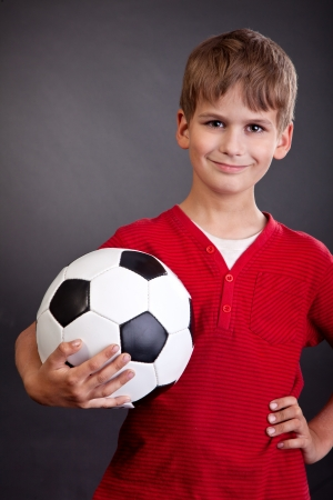 Cute boy is holding a football ball made of genuine leather  isolated on a black background. Soccer ball photo