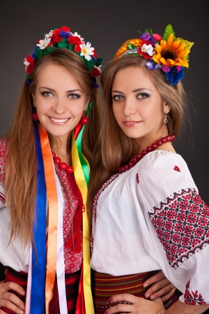 national costume: Young women in ukrainian clothes, with garland  on black background