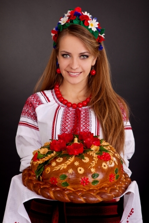 Young woman in ukrainian clothes, with garland and round loaf on black background photo