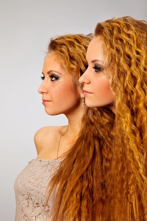 adult sisters: Sttudio shot portrait on isolated background of two sisters twin women friends