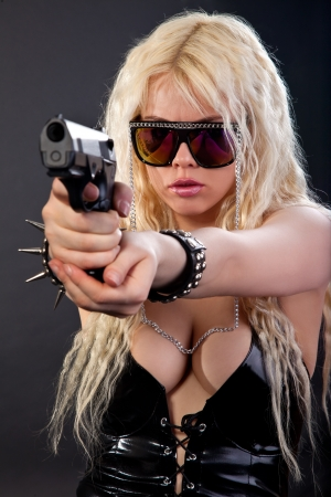 Beautiful sexy girl with gun isolated on black background photo