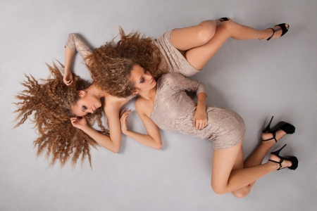 sexy woman on bed: Two beautiful girls twins, isolated on the grey background