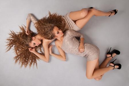 lesbische m�dchen: Zwei sch�ne M�dchen Zwillinge, auf dem grauen Hintergrund isoliert