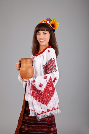 Attractive woman wears Ukrainian national dress is holding a jug isolated on a white background photo