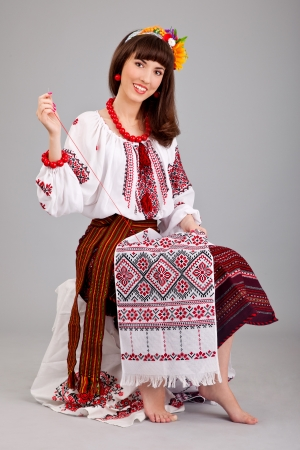 Attractive woman wears Ukrainian national dress is sewing isolated on a white background photo