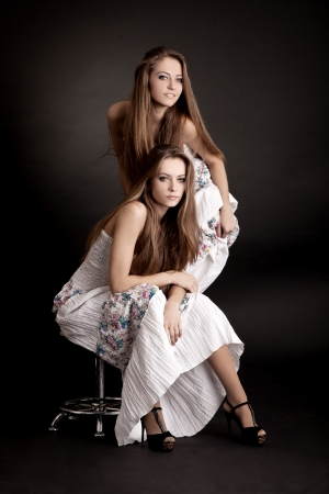 Two beautiful girls twins, isolated on the grey background photo