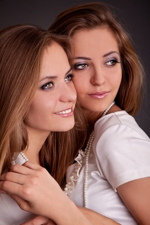 2 persons: studio shot portrait on isolated background of two sisters twin women friends holding in arms each other Stock Photo