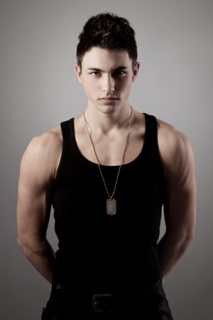A good looking, muscular built, man on a black background with dog tags. photo