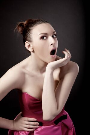 Portrait of a young woman with a astonish expression, isolated over black background photo